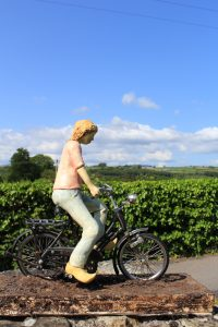 sculpture of girl on bicycle against blue sky. Corina Duyn healing art books and art