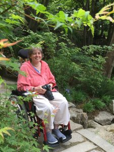 Corina Duyn, with camera in hand, seated in wheelchair - birds make her smile