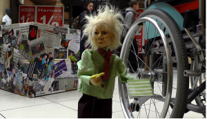 puppet standing beside wheelchair with Disability Box in background. puppetry Project Artist and writer Corina Duyn
