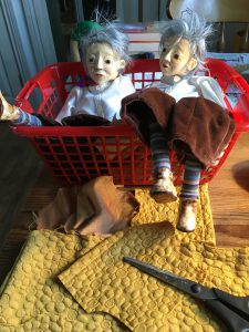 Two puppets lying in a basket waiting for their clothing to be finished